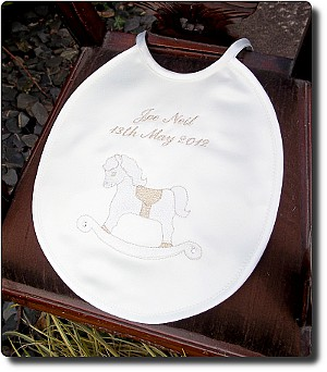 Cream satin bib with rocking horse design